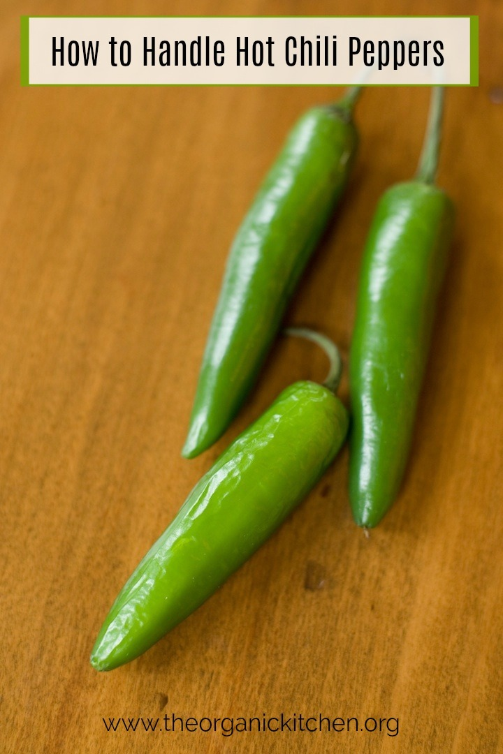 How to Handle a Hot Chili Pepper! Three green serrano chilis on a brown table