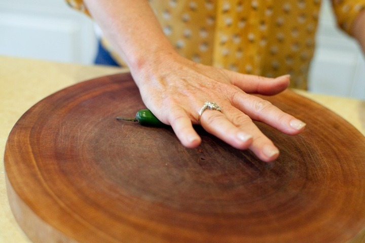 How to Handle a Hot Chili Pepper: a woman's hand rolling a serrano chili on a cutting board