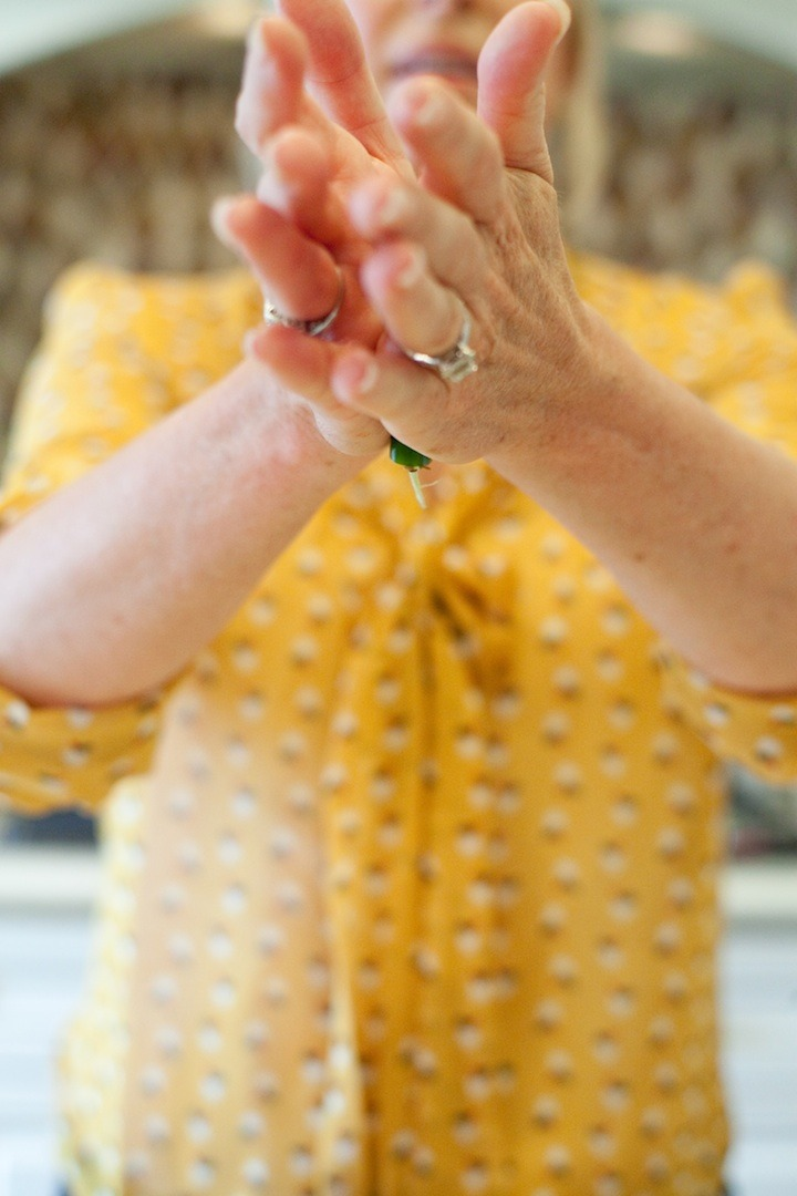 How to Handle a Hot Chili Pepper: a woman rolling a chili pepper between her hands to release the seeds