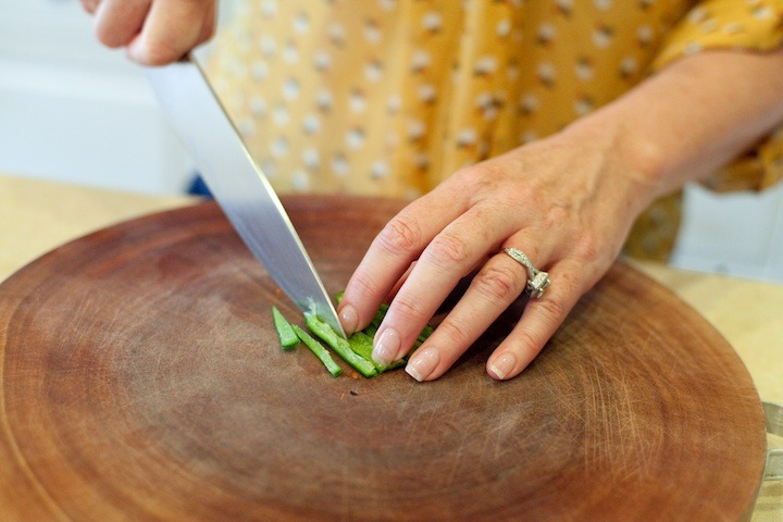 How to Handle a Hot Chili Pepper: a woman's hands slicing a serrano chili with a knife on a cutting board