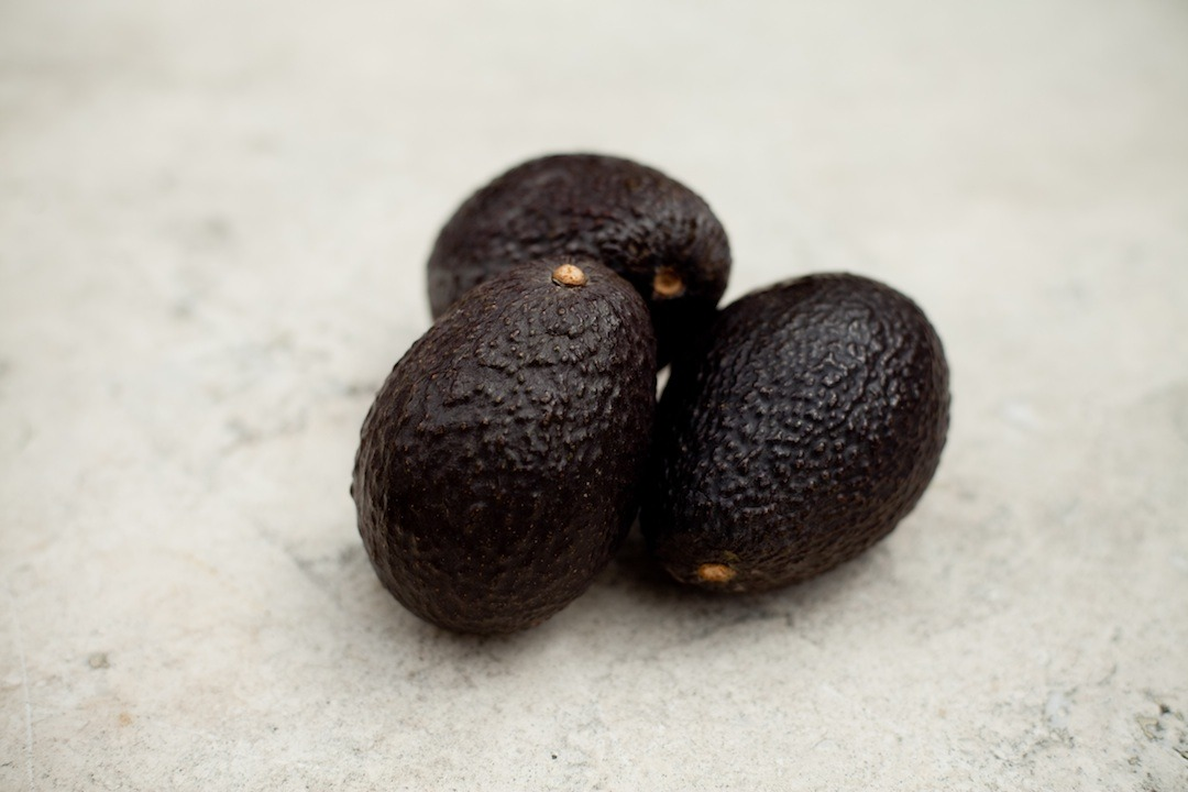 Three ripe avocados on marble table top: How to slice an avocado