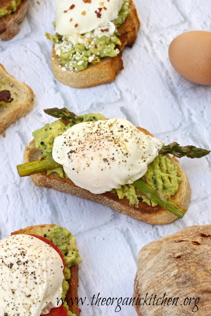 Avocado Toast with Perfectly Poached Eggs and asparagus on white backdrop
