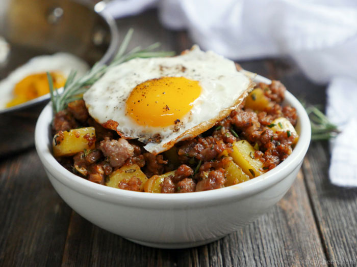 aA white bowl of breakfast hash with a fried egg on top as part of 12 Healthy, Delicious (Whole 30) Breakfast Recipes!