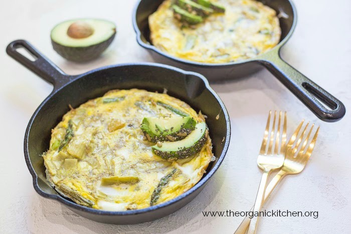 Sliced avocados on frittatas in black cast iron pans