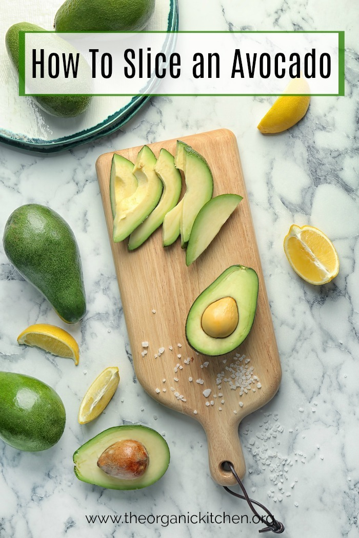 How to slice an avocado: A marble surface with a cutting board with half and avocado and avocado slices on it, surrounded by avocados and oranges